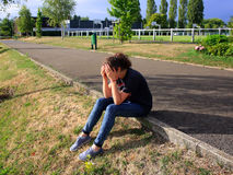 Upset girl sitting in school yard Royalty Free Stock Photo