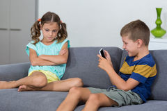 Upset girl sitting on sofa while boy using mobile phone in living room Stock Photos