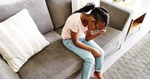Upset girl sitting on sofa in corridor. At hospital stock video footage