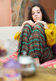 Upset girl on sofa at home Stock Photos
