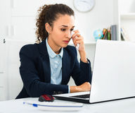 Upset girl solving business problems  with laptop Royalty Free Stock Images