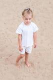 Upset girl standing on the sand Stock Image