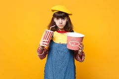 Upset girl teenager in french beret, denim sundress holding plastic cup of cola or soda bucket of popcorn isolated on. Yellow background. People sincere stock photos