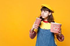 Upset girl teenager in french beret looking aside, holding plastic cup of cola or soda, bucket of popcorn isolated on. Yellow background. People sincere stock images