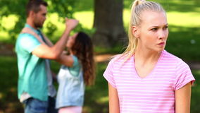 Upset girl watching her crush flirt with another girl stock video