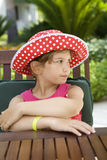 Upset girl wearing Panama sitting at table Stock Photos