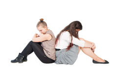 Upset girls sitting back to back Royalty Free Stock Image