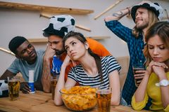 upset group of multiethnic friends in soccer ball hats watching football match royalty free stock photography