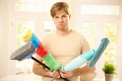 Upset guy with cleaning tools Royalty Free Stock Photos