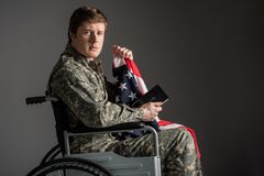 Upset handicapped veteran feeling helpless. Sad disabled soldier sitting in invalid chair and looking at camera with frustrated look. He is holding usa flag and Stock Photos