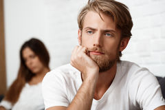 Upset handsome man in quarrel with his girlfriend background. Upset young handsome men in quarrel with his girlfriend on sofa background Stock Image