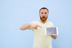 Upset Handsome young man with a beard showing something on a tablet  on a blue background, bright and light Royalty Free Stock Image