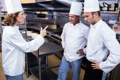 Upset head chef talking to her team Stock Photo