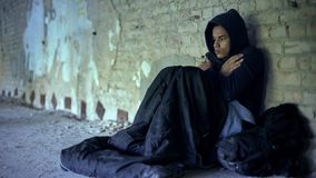Upset homeless teenager wearing hoodie, feeling cold, indifference and poverty. Stock photo stock photos
