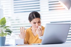 Upset ill woman having a running nose and trying to work in the office. Irritating condition. Young unhappy ill woman feeling unwell while sitting in front of a Royalty Free Stock Photos