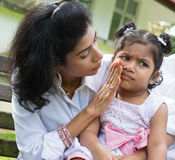 Upset Indian girl. Indian family outdoor. Parent is comforting her crying child Stock Photography