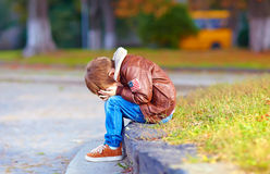 Upset kid boy sitting alone in city park Royalty Free Stock Photography