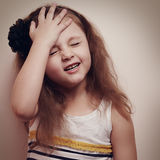 Upset kid girl thinking with hand on the head. Vintage color por Royalty Free Stock Image