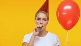 Upset lady in birthday hat holding balloon and blowing in party horn, loneliness