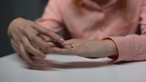 Upset lady pulling wedding ring from finger, broken relations, unhappy marriage. Stock footage stock footage