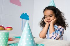 upset little african american girl sitting alone at birthday royalty free stock image