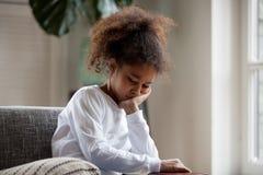 Upset little african girl feeling sad sitting alone at home. Upset little african american girl feels hurt sad bored sitting alone at home, depressed punished stock photo