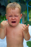 Upset little baby boy crying outdoors stock images