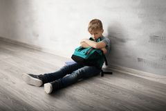 Upset little boy with backpack sitting on floor indoors . Bullying in school. Upset little boy with backpack sitting on floor indoors. Bullying in school stock image