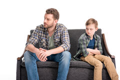 Upset little boy with crossed arms and father sitting on sofa and looking away. Family problems concept Royalty Free Stock Photos