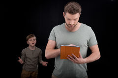 Upset little boy gesturing and looking at father using digital tablet Stock Photo