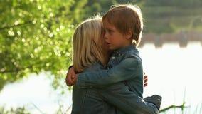 Upset little boy hugging his mother at summer park.  stock video