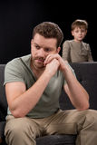 Upset little boy looking at pensive father sitting on sofa and looking away. Family problems concept royalty free stock photo