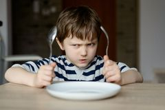 Upset little boy waiting for dinner Royalty Free Stock Photography