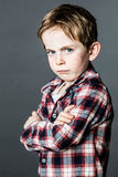 Upset little child standing, pouting and sulking to express attitude Stock Photos