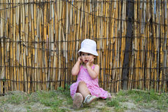 Upset little girl covering her mouth with palms stock images