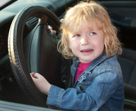 Upset little girl crying in the car, in soft focus Stock Images