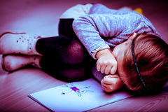 Upset little girl curled up next to her drawing stock photography