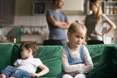 Upset little girl feeling sad after fight with brother. Sitting on sofa with worried parents on background, sulky frustrated sister ignoring child boy royalty free stock photo