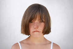 Upset little girl having quarrel with her parents, looking innocently into camera while curving her lips isolated over white backg. Round. Sorrorful female child stock image
