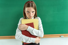 Upset little girl holding school books Royalty Free Stock Image