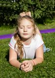 Upset little girl lies on green grass and thinking about stock photos
