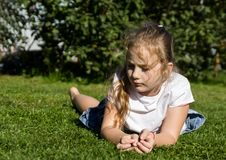 Sad child lies on grass in public park royalty free stock photo