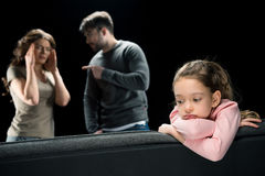 Upset little girl sitting on couch while parents quarreling Royalty Free Stock Photo