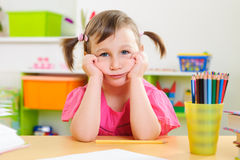 Upset little girl sitting at desk Stock Images