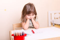 Upset little girl sitting at the desk at school Royalty Free Stock Photo
