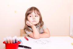 Upset little girl sitting at the desk at school Royalty Free Stock Photos