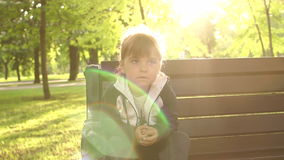 Upset little girl sitting on Park bench at sunset. stock video footage