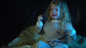 A little girl in striped pajamas at night in her room sits on the bed and cries. A upset little girl in striped pajamas sits on the bed at night in her room and stock footage