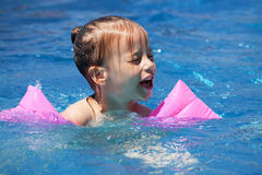 Upset little girl swimming in the pool. Royalty Free Stock Photo