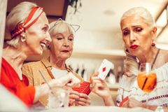 Upset long-haired old woman showing her cards during gambling game royalty free stock image